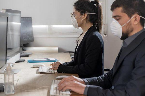 Lavoratori in ufficio con mascherina per tutela COVID 19